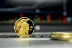 Guld- jättebitcoinmynt med guld- mynt som omkring ligger på ett silvertangentbord av bärbar dator- och diagramdiagramgrafen på a royaltyfri foto