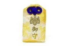 Guld- japansk lyckaomamoriamulett på vit bakgrund Fotografering för Bildbyråer