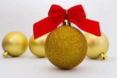 Guld- jul klumpa ihop sig med det röda bandet på vit bakgrund Fotografering för Bildbyråer