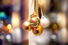 Guld- jul klumpa ihop sig på vitt, och guld- snör åt Arkivfoton