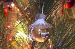 Guld- jul klumpa ihop sig, som har en malaform, på julgranen Arkivfoton