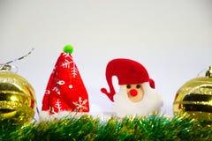 Guld- julbollar, jultomten i en röd hatt i mitt och jultillbehören Arkivfoto