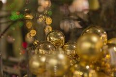 Guld- julbollar som hänger i ett träd arkivbilder