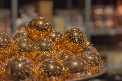 Guld- julbollar som ligger i en bunke royaltyfri bild