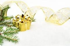Guld- julgåvor med guld- band- och visargran på snö fotografering för bildbyråer