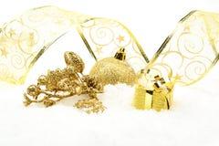 Guld- juljärnek lämnar gåvan på snö royaltyfri foto