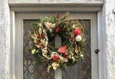 Guld- julkrans på en vit dörr royaltyfria bilder