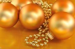 Guld- julprydnader på guld- bakgrund Royaltyfria Bilder