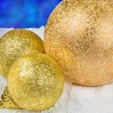 Guld- julpynt på snö i form av bollar Royaltyfria Bilder