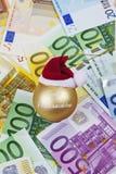 Guld- julsfär med jultomten hatt överst på hög av euroanmärkningar Arkivbilder