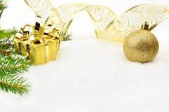 Guld- julstruntsaker med och visargran och band på snö arkivbilder