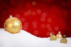 Guld- julstruntsaker på snö med en röd bakgrund arkivfoton