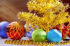 Guld- julträd med dekorerade bollar och ljusa strålar på mörk bakgrund Royaltyfri Fotografi
