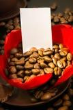 Guld- kaffebönor i den röda blomman för knopp, papper med ditt häfte Royaltyfria Foton