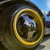Guld- kant och svart eker på bilhjul för en svart fotografering för bildbyråer
