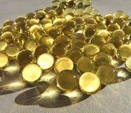 Guld- kapslar Arkivbild