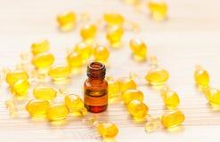 Guld- kapslar av naturlig cosmetik för framsida och den 1 ml flaskan med nödvändig olja på det trä Royaltyfri Fotografi