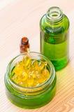 Guld- kapslar av naturlig cosmetik för framsida och flaskor med closeupen för nödvändiga oljor Fotografering för Bildbyråer