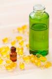Guld- kapslar av naturlig cosmetik för framsida och flaskor med nödvändiga oljor på det trä Fotografering för Bildbyråer