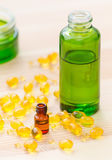Guld- kapslar av naturlig cosmetik för framsida och flaskor med nödvändiga oljor på träbakgrunden Arkivfoto
