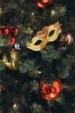 Guld- karnevalmaskering som en julgranleksak royaltyfria bilder