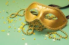 Guld- karnevalmaskeringar med pärlor på en grön bakgrund Arkivfoton