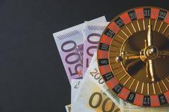 Guld- kasinotema Bild av kasinorouletten, pokerlekar, pengar på tabellen som är all på en mörk bokehbakgrund Ställe för utskrift fotografering för bildbyråer