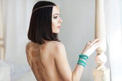 Guld- kedja i händerna av en ung attraktiv orientalisk kvinna Görande suddig bakgrund Royaltyfri Foto