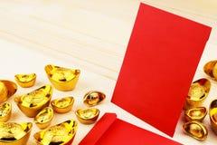 Guld- kinesisk tacka Yuan Bao och tomma röda kuvert på träbakgrund arkivbild
