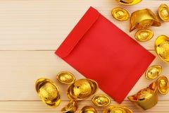 Guld- kinesisk tacka Yuan Bao och tomma röda kuvert på träbakgrund arkivfoton