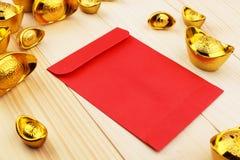 Guld- kinesisk tacka Yuan Bao och tomma röda kuvert på träbakgrund arkivfoto
