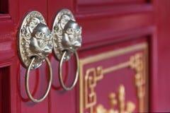 Guld- kinesiska dörrknackare på en röd dörr Arkivbilder