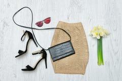 Guld- kjol, skor, exponeringsglas och en bukett av påskliljor Mode Royaltyfri Bild