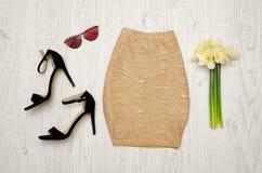 Guld- kjol, skor, exponeringsglas och en bukett av påskliljor trendigt begrepp spelrum med lampa Arkivfoton