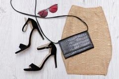Guld- kjol, skor, koppling och exponeringsglas trendigt begrepp spelrum med lampa Royaltyfri Bild