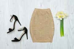 Guld- kjol, skor och en bukett av påskliljor Conc innegrej Royaltyfria Foton