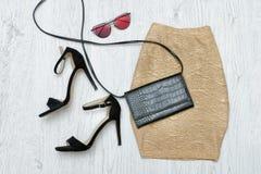Guld- kjol, skor och exponeringsglas trendigt begrepp Träbac Arkivfoto