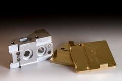 Guld- klar CNC och silvermetalldetalj på vit bakgrund med skugga Royaltyfria Bilder