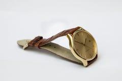 Guld- klocka för man` s med läderremmen som isoleras på vit bakgrund Arkivbild