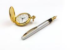 Guld- klocka och penna fotografering för bildbyråer