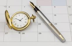 Guld- klocka och penna Arkivfoton
