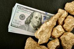 Guld- klumpar och USA-dollar på ett svart bakgrundsläder. Clo Arkivfoton