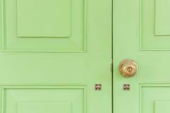 Guld- knopp för tappning på den gröna dörren arkivfoton