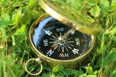 Guld- kompass på gräs Arkivfoto