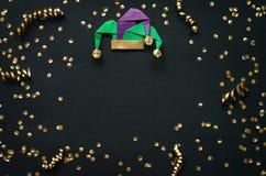 Guld- konfettier, gyckelmakaremaskeradhatt Mardi Gras vykort för April Fools Day feriegarnering, hälsning, inbjudankort, baner arkivfoto