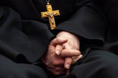 Guld- kors med korsfästelse av Jesus på bröstkorgen av en präst i svart kläder Symbolet av den ortodoxa religionen Händer royaltyfria bilder