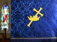 Guld- kors till och med kronan på blått baner med Jesus det bra herdefönstret arkivbild