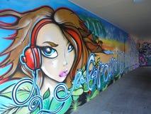 Guld kostar Queensland Australien November 22 2017 grafitti lyssnande musik för den vägg- väggunga flickan royaltyfria bilder