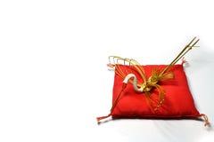 Guld- kran för nytt år på den röda kudden Arkivbild