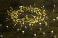 Guld- krona av taggar på riden ut brun bakgrund med pärlor s Royaltyfria Foton